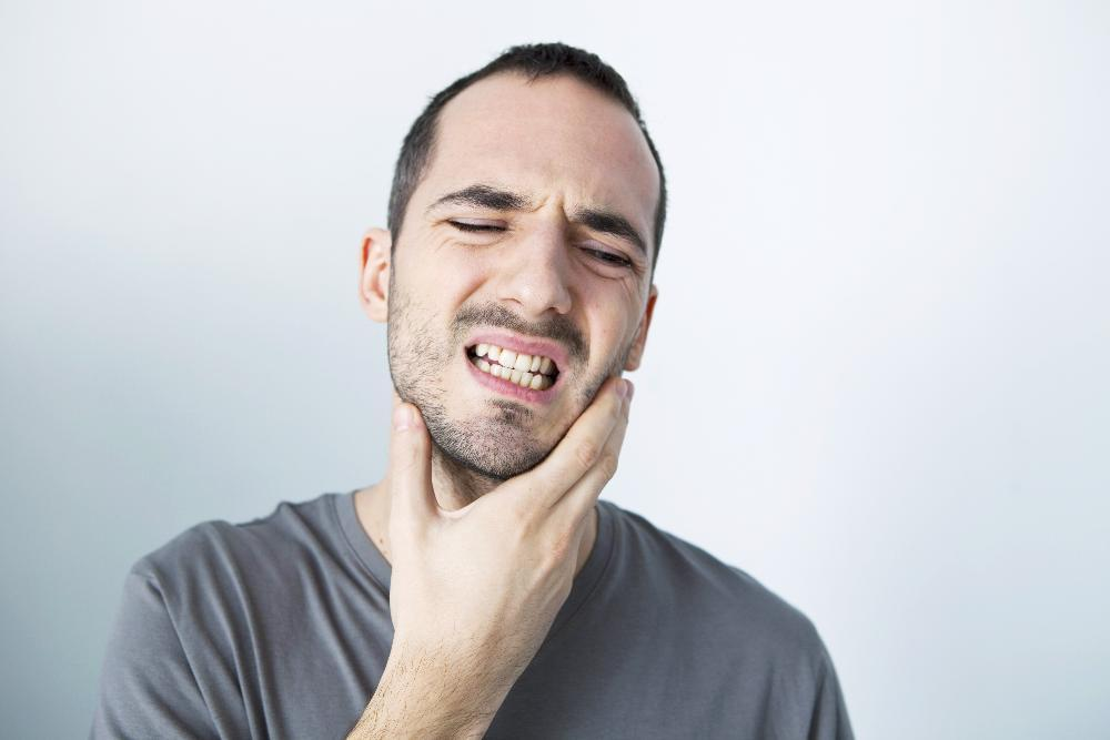 Man with bad tooth pain from dental emergency near Champaign IL