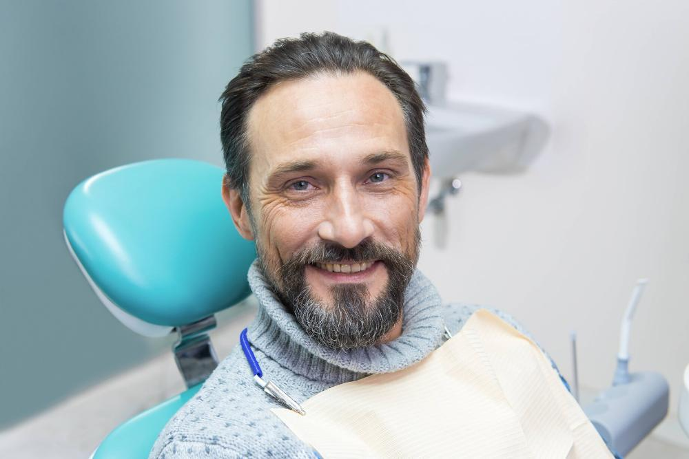 man smiling in dental chair after getting a filling