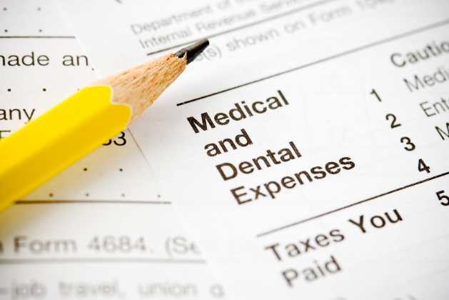 Pencil laying on financial bills near affordable dental care in Champaign IL