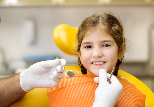 Young girl smiling at dental exam with our children's dentist in Champaign IL