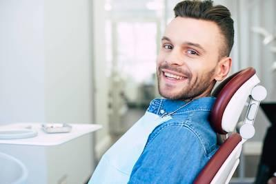 Patient smiling in treatment chair for same day dental crowns in Champaign