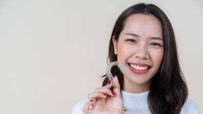 Woman holding SureSmile clear aligners | Clear Braces in Champaign IL